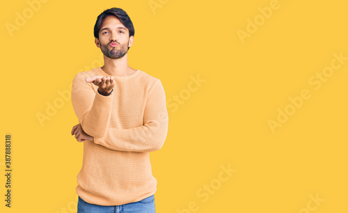 Obraz na plátně Handsome hispanic man wearing casual sweater looking at the camera blowing a kiss with hand on air being lovely and sexy