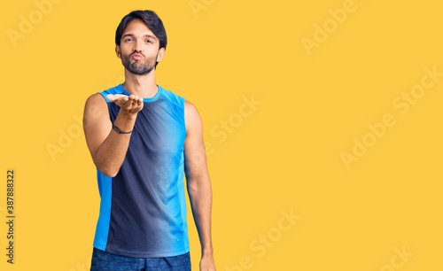 Fotografie, Obraz Handsome hispanic man wearing sportswear looking at the camera blowing a kiss with hand on air being lovely and sexy