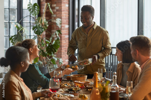 Obraz Portrait of smiling African-American man serving food while hosting dinner party with friends and family at home, copy space - fototapety do salonu