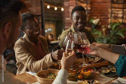 Obraz Portrait of happy African-American couple clinking glasses while enjoying dinner party with friends and family in cozy interior - fototapety do salonu