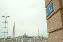 Notre Dame De La Garde Church, Also Called Bonne Mere, Seen From The Rue De La Mairie Street (meaning In French City Hall Street) With Boats Of The Vieux Port In Front, In Marseille, Southern France