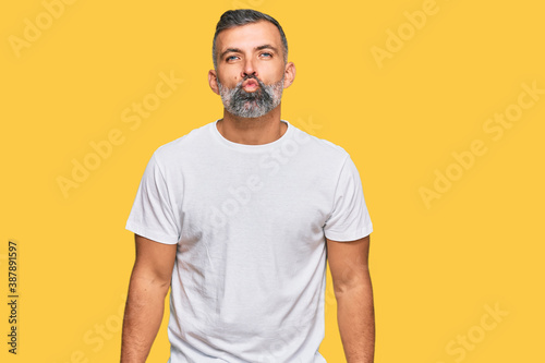 Fototapeta Middle age handsome man wearing casual white tshirt looking at the camera blowing a kiss on air being lovely and sexy