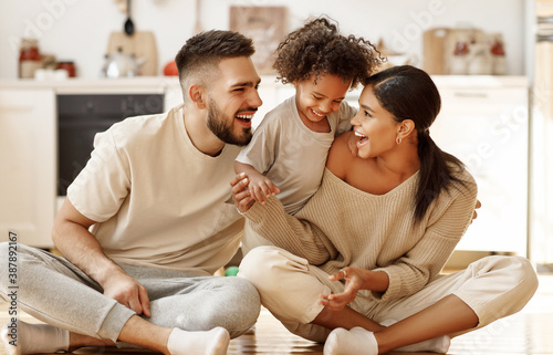 Leinwand Poster happy multiethnic family mom, dad and child  laughing, playing and tickles    on floor in cozy kitchen at home