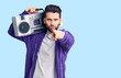 canvas print picture Young handsome man with beard listening to music using vintage boombox pointing with finger to the camera and to you, confident gesture looking serious