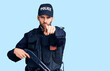 canvas print picture Young handsome man with beard wearing police uniform holding shotgun pointing with finger to the camera and to you, confident gesture looking serious