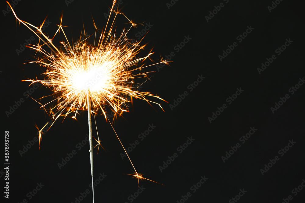 Fototapeta Bright burning sparkler on black background, closeup. Space for text