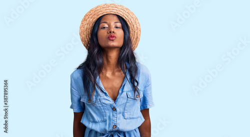 Fotografie, Obraz Young indian girl wearing summer hat looking at the camera blowing a kiss on air being lovely and sexy