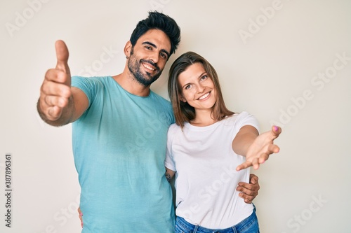 Fotografie, Obraz Beautiful young couple of boyfriend and girlfriend together looking at the camera smiling with open arms for hug
