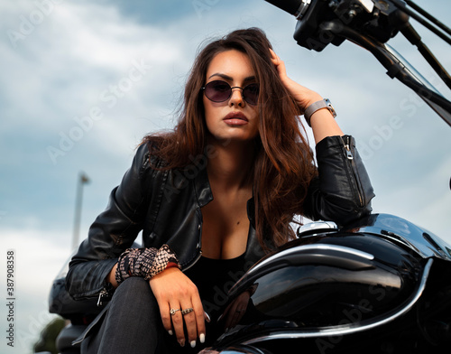 Obraz Closeup portrait of attractive, sensual girl in leather jacket posing on motorcycle - fototapety do salonu