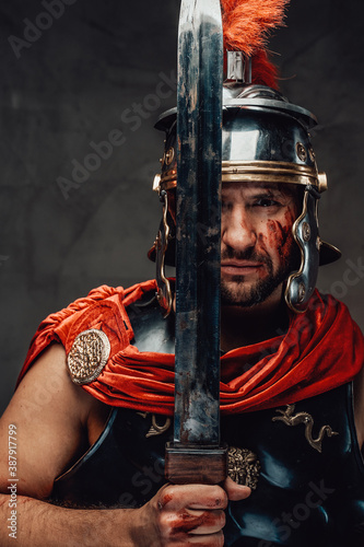 Photo Serious military roman with dark armour and helmet posing using his sword in dark background
