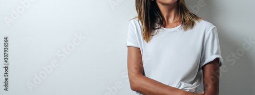 Young and pretty woman in white blank t-shirt wearing glasses, empty wall, horizontal studio portrait Fototapet