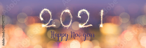 Obraz Happy new year 2021 written with sparkles on panoramic banner of blurred bokeh holiday lights at night - fototapety do salonu