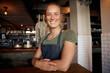 Leinwandbild Motiv Cheerful young female waitress wearing apron standing leaning on table in cafe