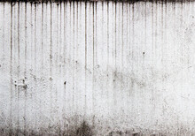 Vertical Streaks Of Dirt On A White Textured Wall