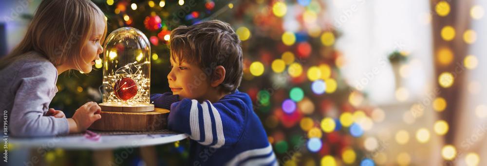 Fotografie, Obraz children on christmas eve in bright decorations