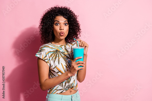 Obraz Photo portrait of shocked woman holding plastic straw paper cup in hands isolated on pastel pink colored background with blank space - fototapety do salonu