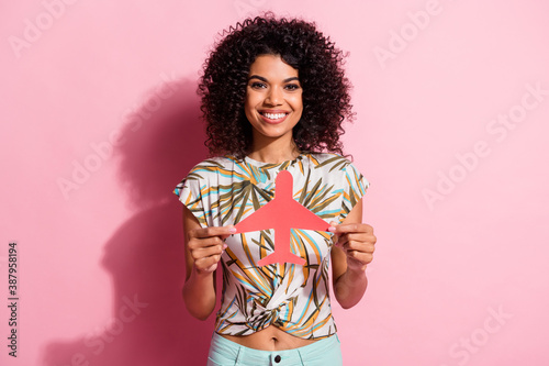 Obraz Portrait photo of pretty black skinned curly woman showing paper plane figure smiling isolated on pastel pink color background - fototapety do salonu