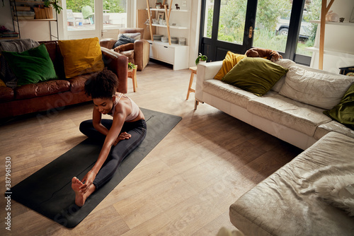 Foto High angle view of young happy woman at home doing stretching exercise