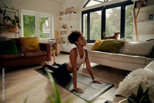 African woman lying on yoga mat at home doing stretching exercise Fototapet