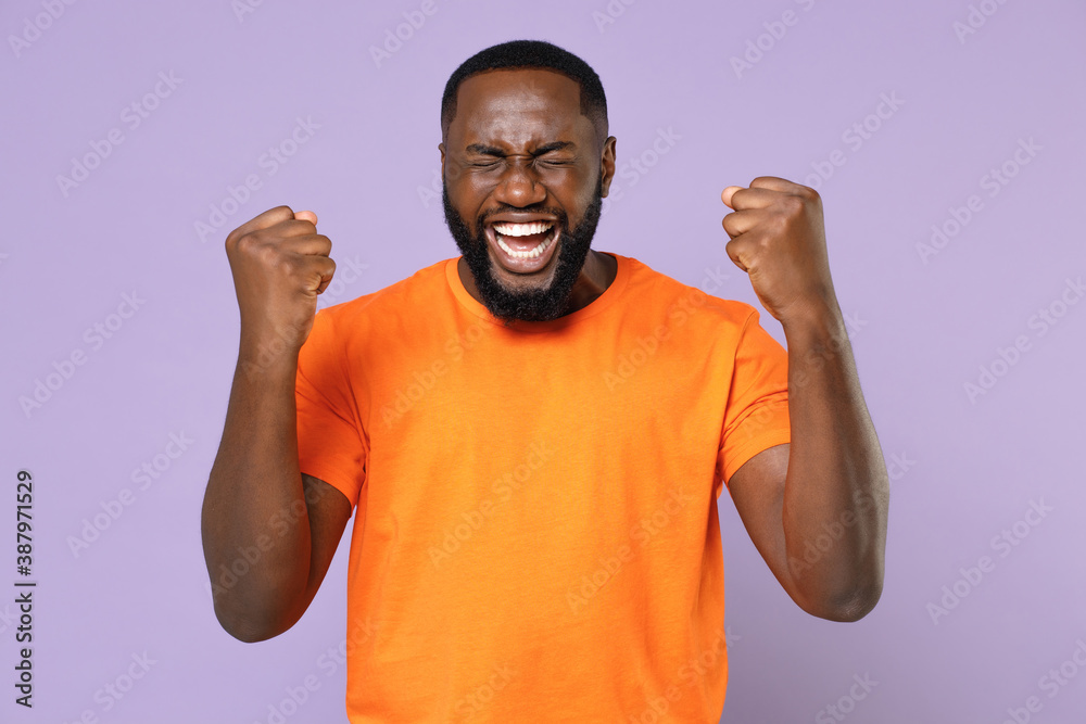 Fototapeta Happy joyful young african american man 20s wearing basic casual orange blank empty t-shirt standing clenching fists doing winner gesture isolated on pastel violet colour background, studio portrait.