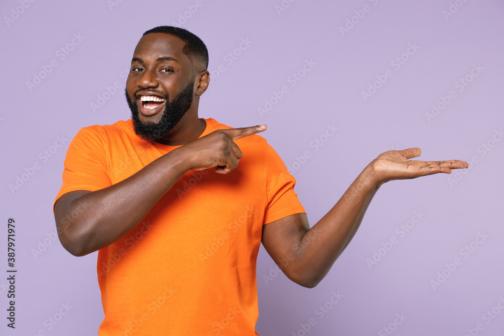 Fototapeta Funny young african american man 20s wearing basic casual orange t-shirt standing pointing index finger hand aside on mock up copy space isolated on pastel violet colour background studio portrait.
