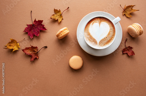 Obraz Cup of coffee and dry leaves on brown background - fototapety do salonu