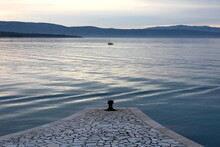 Panoramic View Of Traditional Stone Tiles Covered Pier And Lone Fisherman Fishing On Small Fishing Boat In Middle Of Local Bay Surrounded With Calm Sea And Mountains In Background On Cold Winter Day