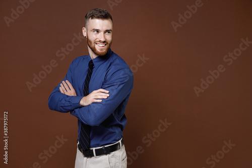 Slika na platnu Side view smiling successful bearded young business man in blue shirt tie holding hands crossed looking aside isolated on brown background studio portrait