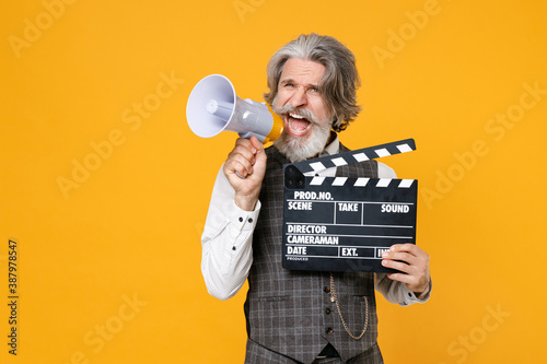 Crazy elderly gray-haired business man in suit waistcoat shirt hold classic black film making clapperboard screaming in megaphone isolated on yellow background Fototapeta