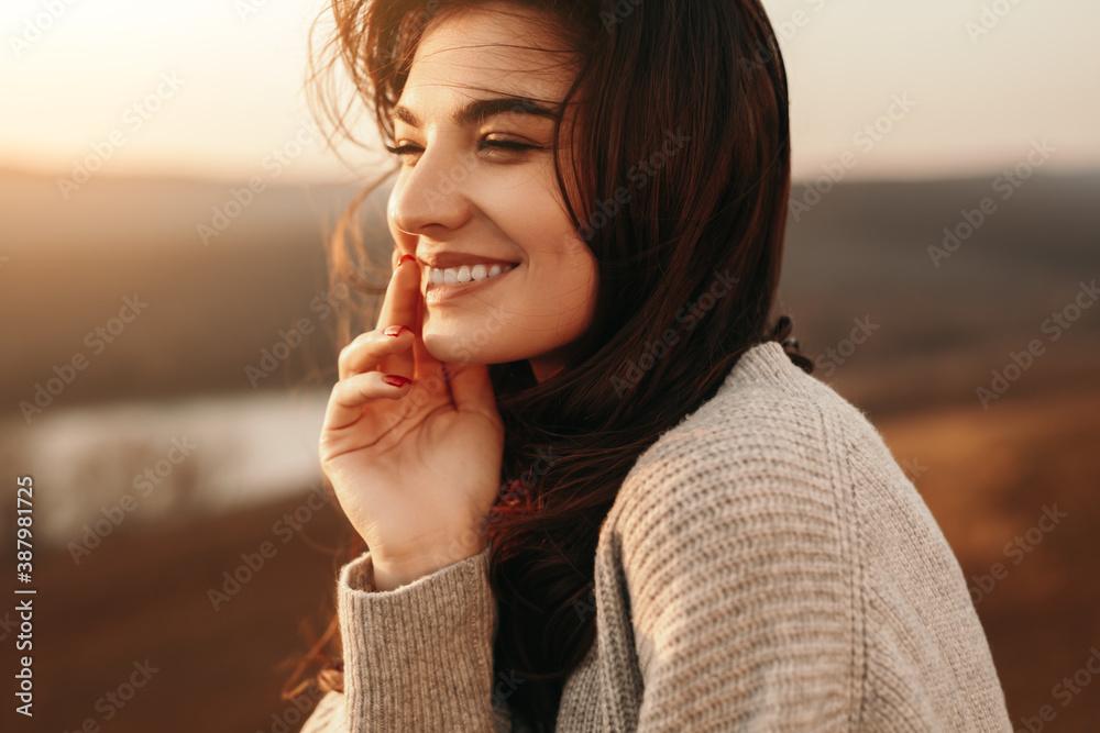 Fototapeta Happy young woman enjoying sunset in nature