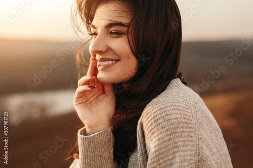 Obraz Happy young woman enjoying sunset in nature - fototapety do salonu