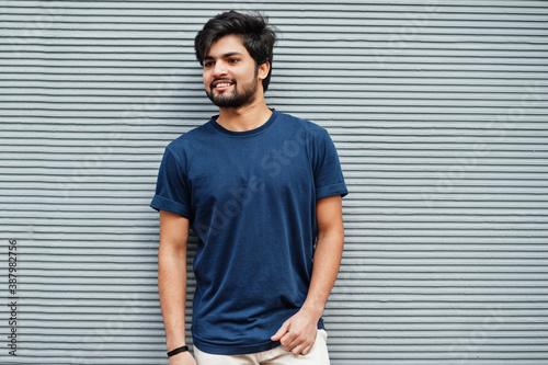Obraz Stylish casual indian man wear blue t-shirt posing against grey wall. - fototapety do salonu