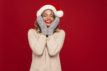 Nice Happy Girl In Santa Claus Hat And Knitted Mittens Grabbing Her Face