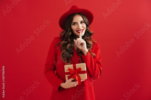 Foto Smiling beautiful woman showing silence gesture and holding gift box
