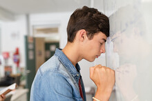 Stressed High School Student Having Difficulty Solving The Equation At White Board