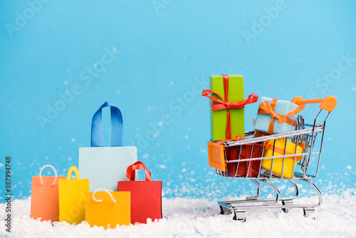 Obraz Tiny paper bags near trolley with bunch of little gifts on blue background, new year concept - fototapety do salonu