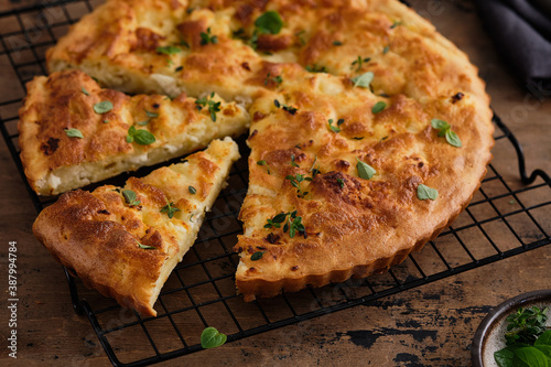 Fotografia Pie or tart with feta cheese on wooden background.