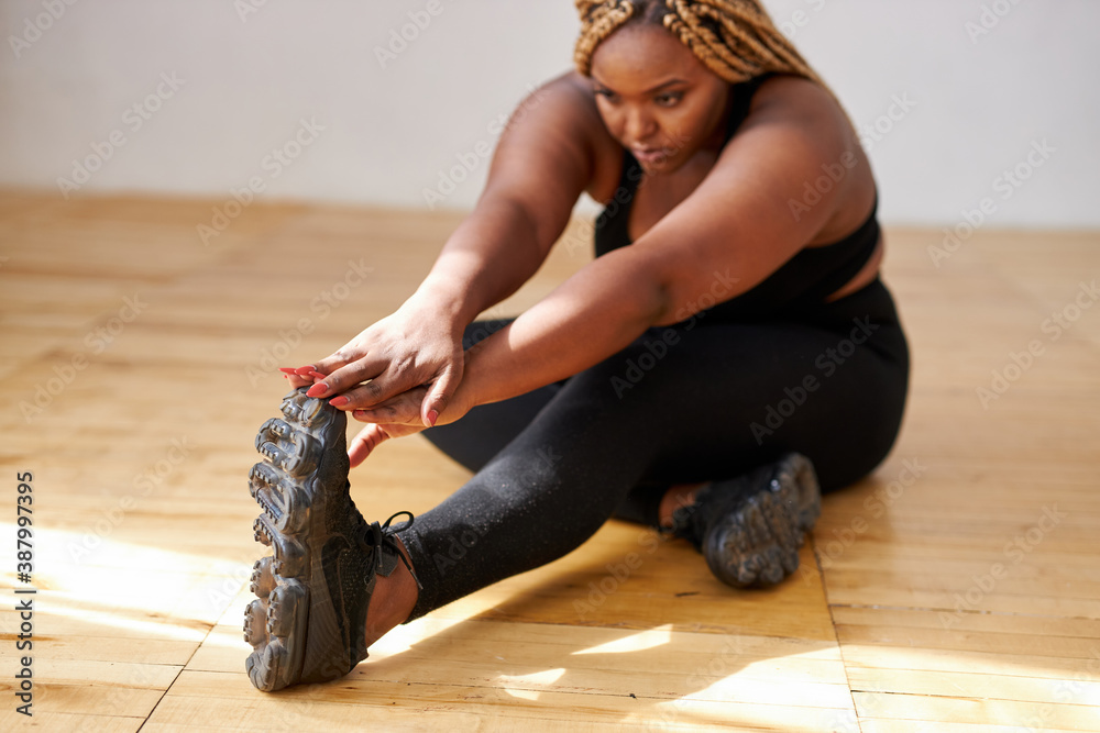Fototapeta chubby african american woman do exercises sitting on the floor, plus size black female model in sportswear engaged in fitness, eant to loss weight