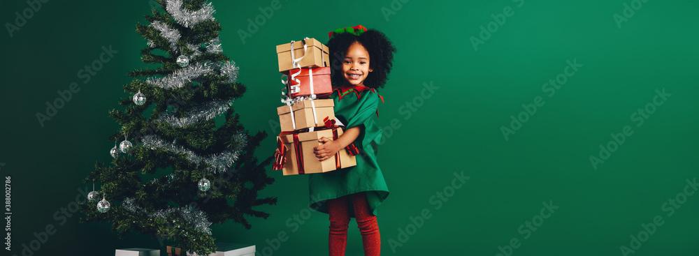 Fototapeta Smiling kid holding a pile of gift boxes