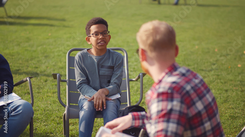 African preteen boy in glasses answering teacher question at outdoors lesson Tapéta, Fotótapéta