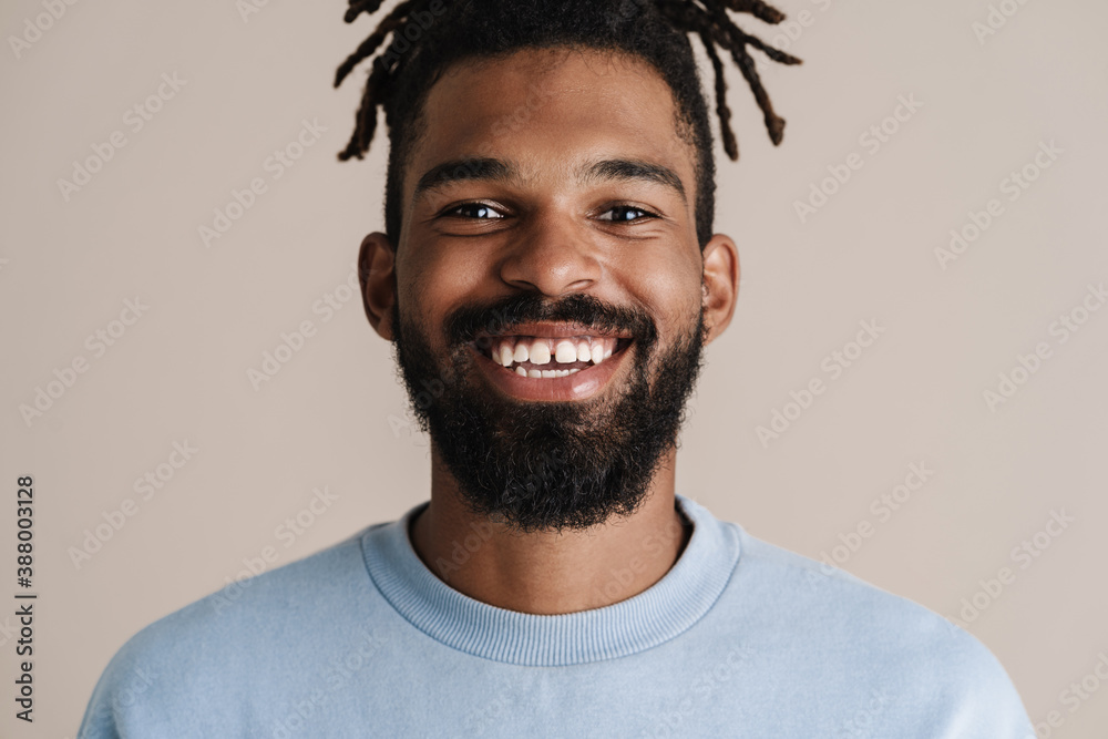 Fototapeta Joyful african american guy smiling and looking at camera