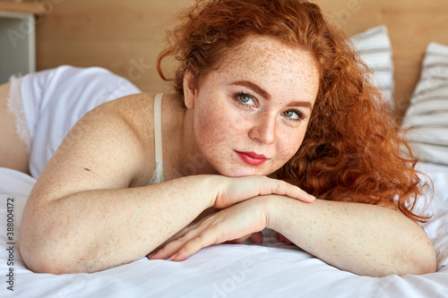 Foto red haired chubby woman in lingerie lies on bed, have rest