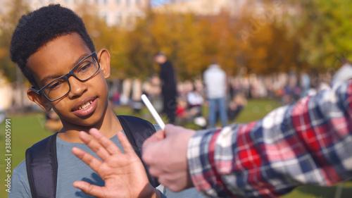 Fototapeta African preteen boy refusing cigarette offered by dealer outdoors