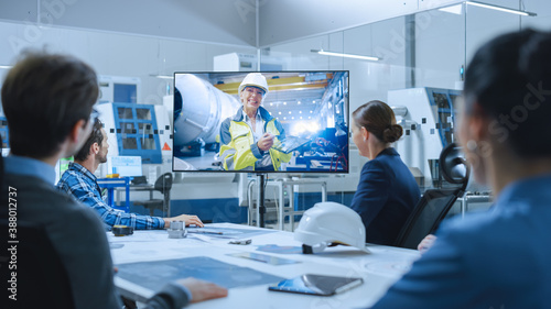 Diverse Group of Specialists, Managers in the Factory Office Meeting Room, Have Conference Video Call with Factory Chief Female Engineer, She Talks about Production Growth, Uses Tablet Computer - 388012737