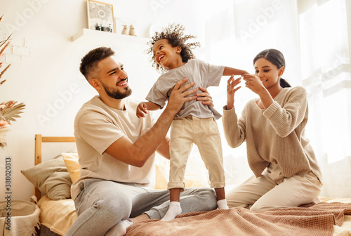 Fotografie, Obraz happy diverse family mom, dad and child  laughing, playing and jumping   in bed   at home