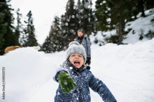 Photo Front view of small child playing in snow, holiday in winter nature