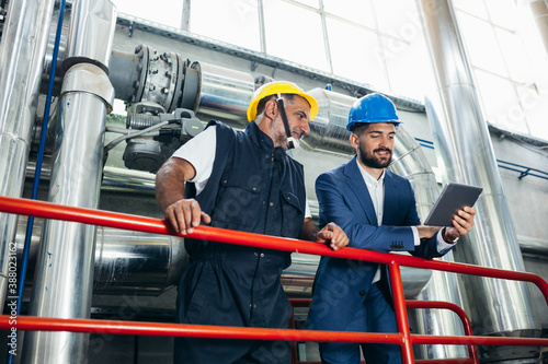 Obraz industry worker and his supervisor talking in heating plant - fototapety do salonu