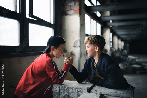 Fototapeta Teenagers boys indoors in abandoned building, arm wrestling.