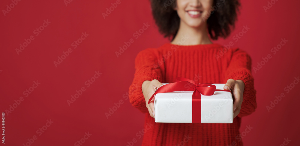 Fototapeta Cropped studio shot portrait of smiling african american female in sweater gives box with gift
