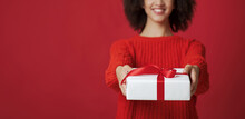 Cropped Studio Shot Portrait Of Smiling African American Female In Sweater Gives Box With Gift